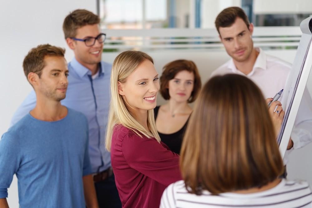 Frau Erklärt einer Lerngruppe Inhalte an einer Flipchart