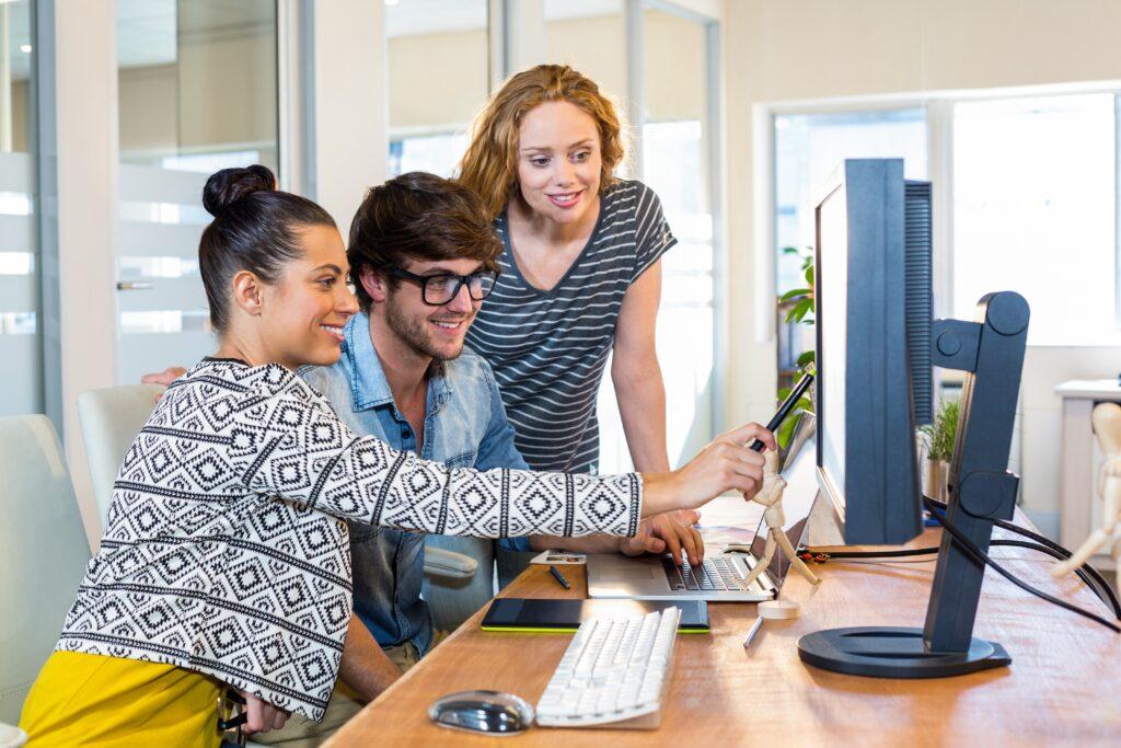 Drei junge Menschen arbeiten zusammen vor einem Bildschirm