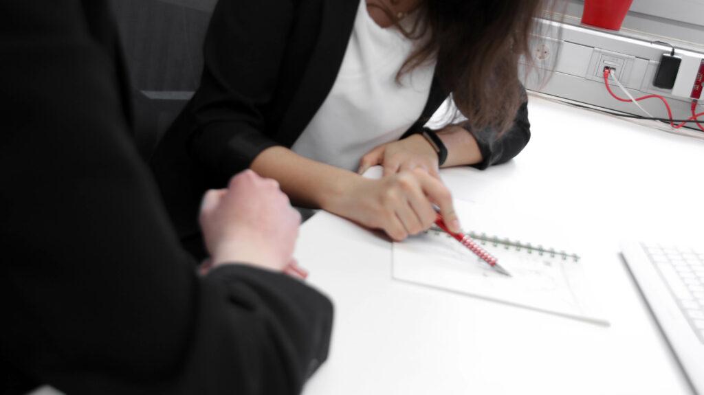 Eine Frau erklärt einer anderen Frau etwas mithilfe eines Blocks und Stiftes