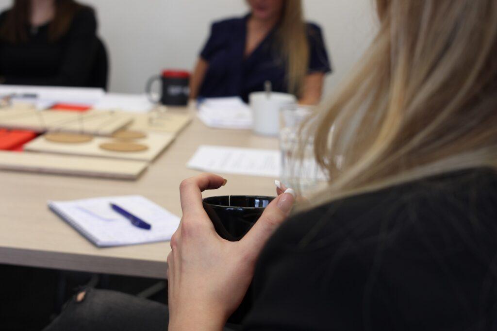 Frau sitzt am Tisch mit einer schwarzen Tasse in der Hand und nimmt in einer Besprechung teil
