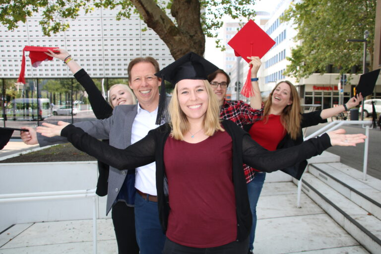 Mehrere Menschen stehen hintereinander und zeigen ihre schwarzen und roten Hüte zur Seite