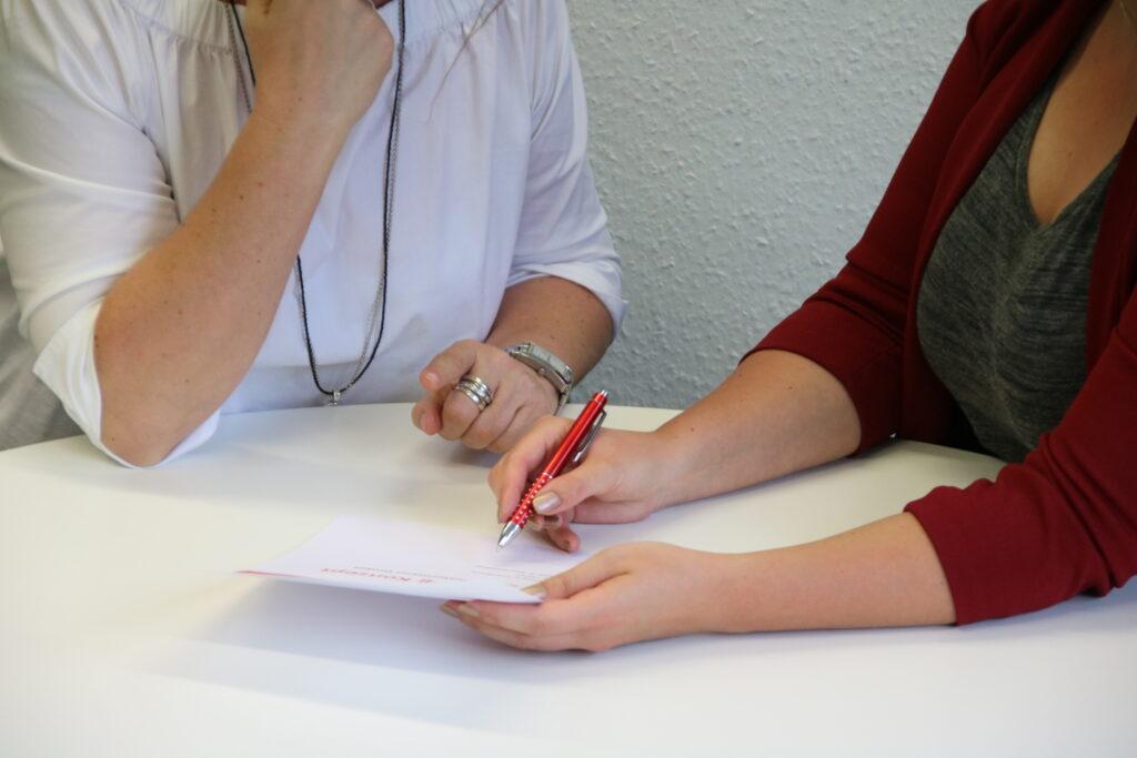 Frauen tauschen sich an einem weißen Tisch über ein Angebot aus