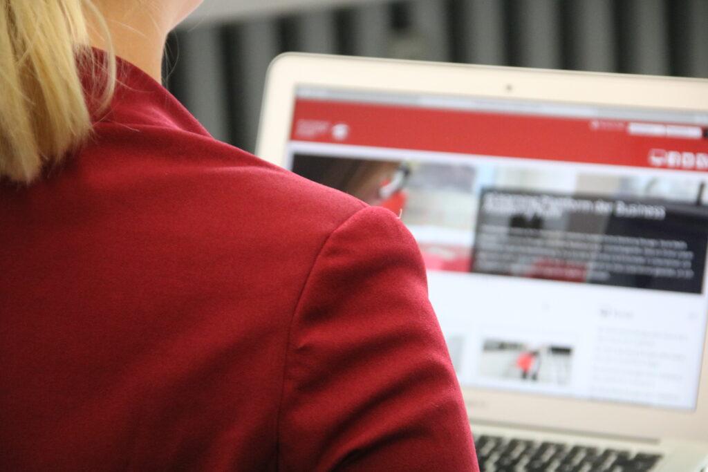 Junge Frau mit roten Balzer sitzt vor einem Laptop