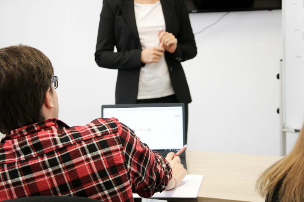 Person verfolgt eine Präsentation einer Frau