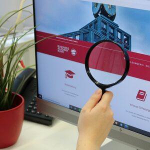 Mit einer Lupe analysiert eine Frau auf einem Bildschirm die Sicherheit auf ihrer Website