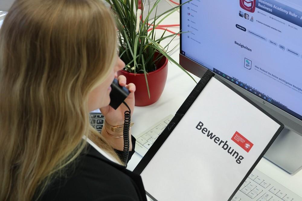 Frau mit schwarzem Blazer sitzt mit Bewerbungsmappe vor dem Bildschirm und telefoniert