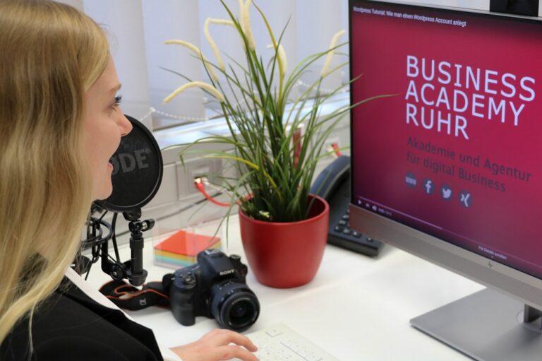 Frau sitzt vor einem Bildschirm mit einem Audioaufnahmegerät und einer Kamera