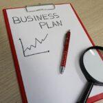 """Weißes Papier auf einem roten Klemmbrett mit der Aufschrift """"Business Plan"""""""