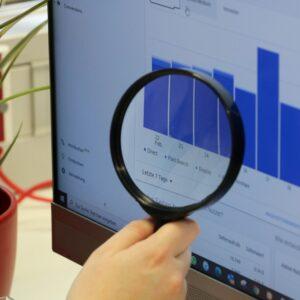 Frau analysiert mit einer Lupe die Google Analytics Auswertungen an einem Bildschirm