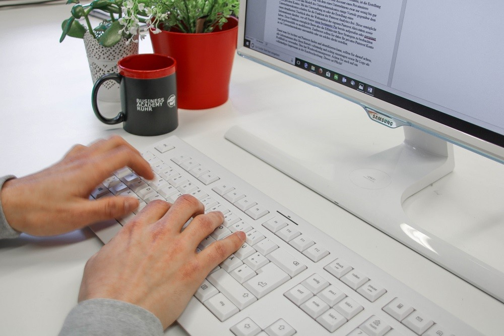 Mann tippt an einer weißen Tastatur einen Blogbeitrag