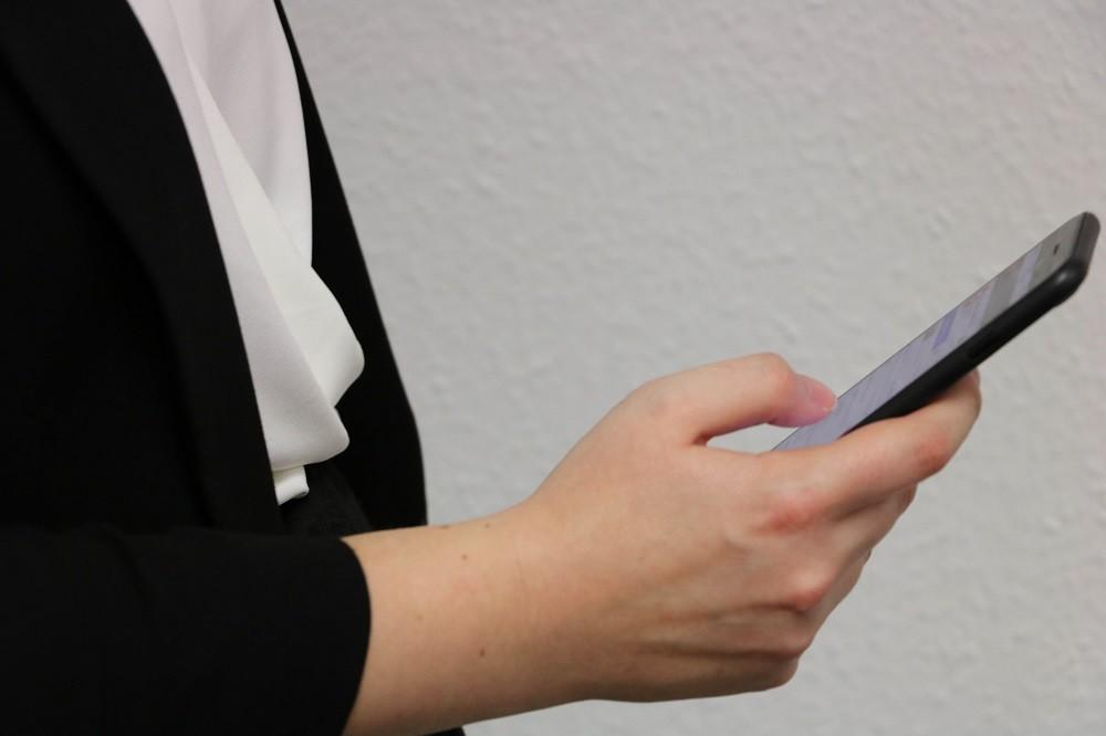 Frau mit schwarzen Blazer und weißer Bluse tippt auf ihrem Smartphone