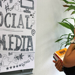 """Frau steht vor einer Flipchart mit der Aufschrift """"Social Media"""""""
