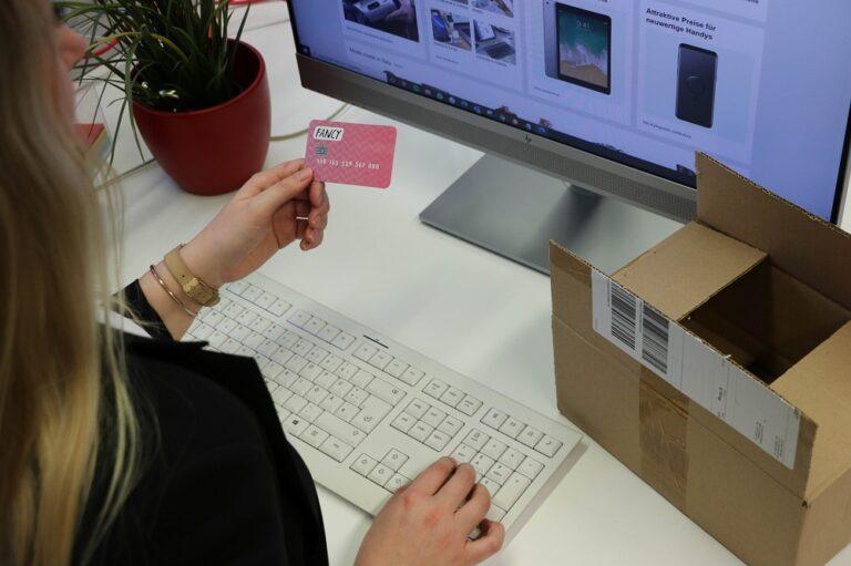 Frau sitzt vor einem Bildschirm mit Onlineshop und schaut auf ihre Kreditkarte