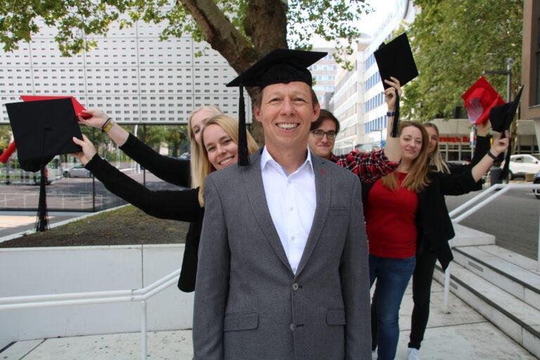 Das Team der Business Academy Ruhr mit Abschlusshüten