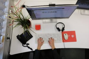 Beispielhafter Arbeitsplatz mit Bildschirm, Tastatur, Telefon und Headset