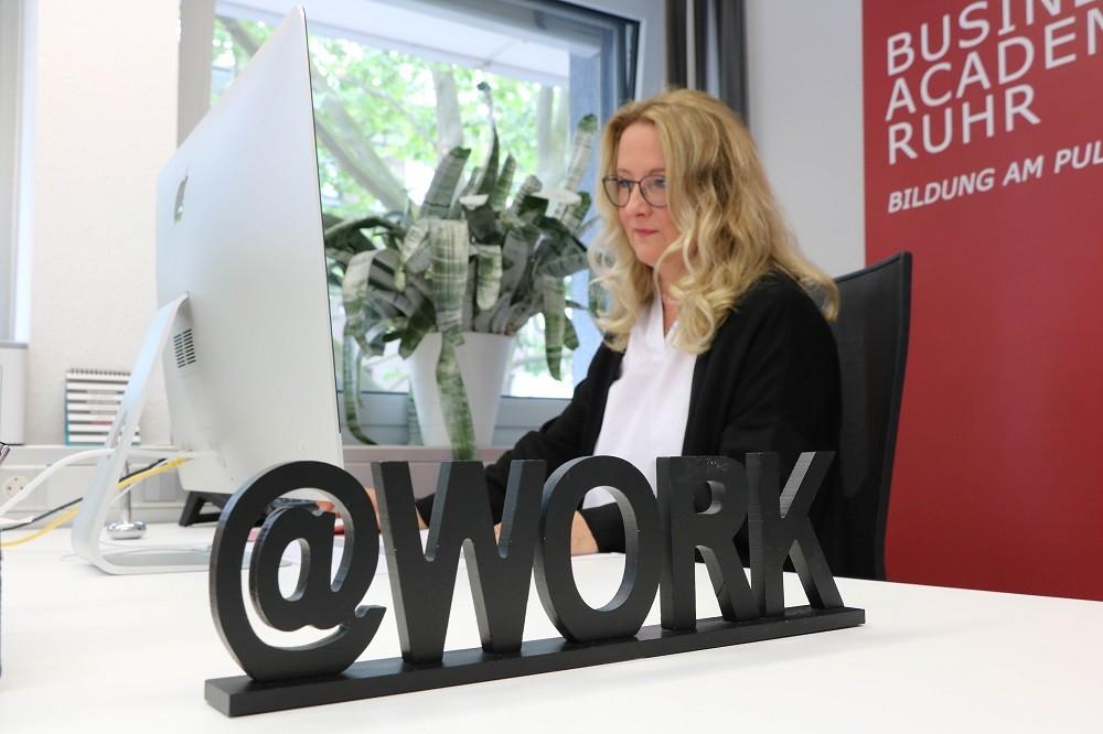 """Marie Huchthausen vor ihrem MAC mit einem """"@Work-Aufsteller"""""""