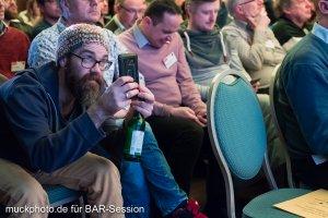 Während des Vortrags werden fleißig Bilder von der Präsentation gemacht - obligatorisch mit einem Bier in der Hand.