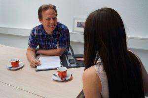 Bei der Erstellung der Facharbeit digitales Marketing wird eine Teilnehmerin der Weiterbildung durch einen Coach beraten