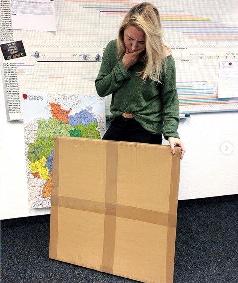 Praktikantin mit großem Paket - sie absolviert ein Praktikum im Bereich Social Media