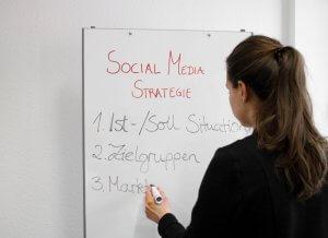 Das Bild zeigt eine Frau bei der Entwicklung einer Social Media Strategie für KMU