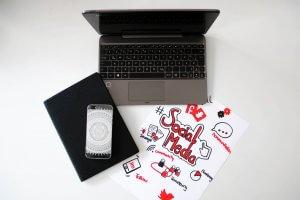 Man sieht einen Laptop, ein Tablet, ein Smartphone und einen Schreibblock. All dies kann helfen bei der Entwicklung einer Social Media Strategie für KMU.