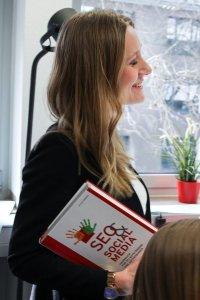 Eine lächelnde Frau mit einem Buch in der Hand. Sie nimmt am blended Learning teil.