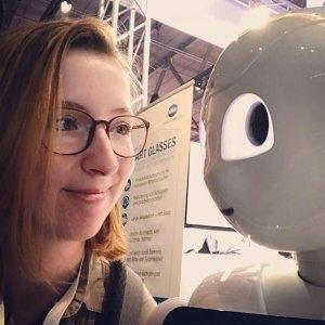 Chatbots in der Weiterbildung - eine junge Frau lächelt einen Roboter bzw. eine künstliche Intelligenz an, die sie in der Bildung berät