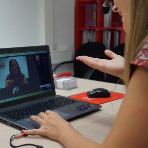 Man sieht eine junge Frau am Computer und ihr Spiegelbild macht die gleiche Geste wie sie. Bei der Nutzung von Chatbots in der Weiterbildung lernen künstliche Intelligenzen dazu und geben die Antworten, die mit höchste Wahrscheinlichkeit zur Frage passen werden.