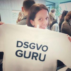 """Das Bild zeigt eine betriebliche Datenschutzbeauftragte zur Umsetzung der Datenschutz Grundverordnung, die ein T-Shirt in die Kamera hält, auf dem """"DSGVO Guru"""" steht."""