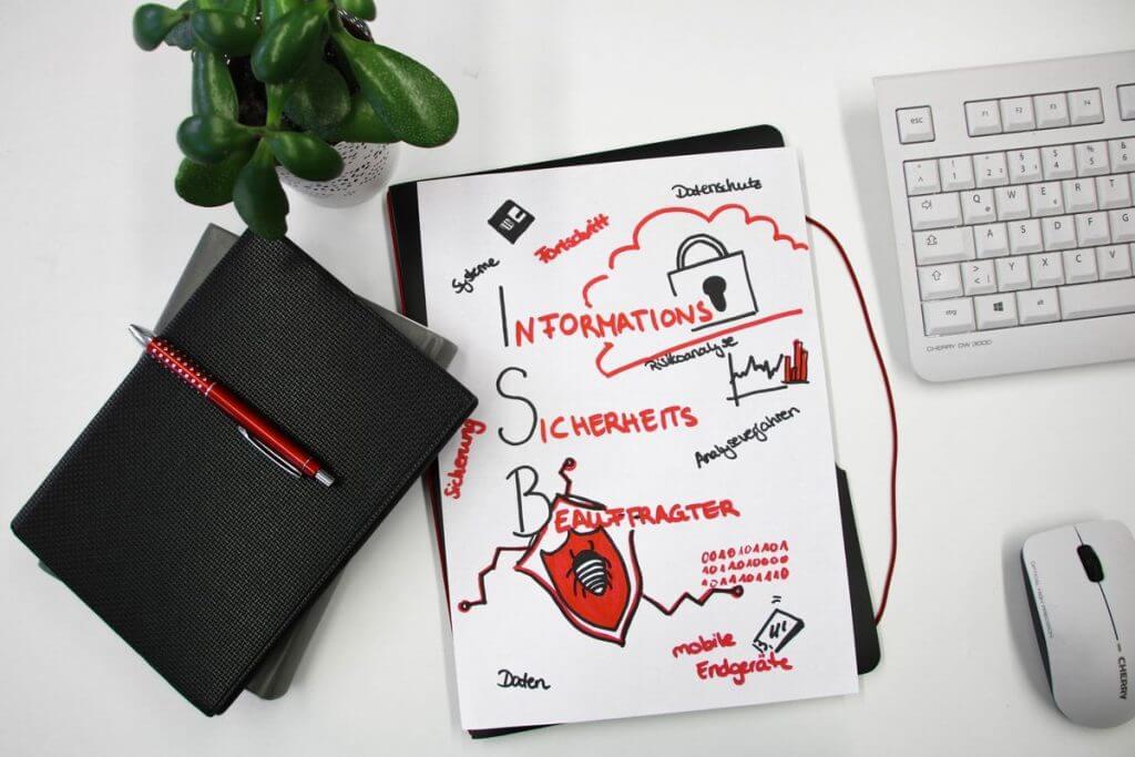 Zur Frage nach dem Unterschied zwischen Datenschutzbeauftragter und IT-Sicherheitsbeauftragter zeigt das Bild einen Notizblock mit Zeichnungen zum Thema Informationssicherheitsbeauftragter sowie eine Tastatur, eine Computermaus und einen Stift auf einem Schreibtisch