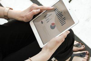 Auf dem Bild ist zu sehen, wie eine Mitarbeitern Dank Digitalisierung in Unternehmen per Tablet PC außerhalb des Unternehmens arbeiten kann.