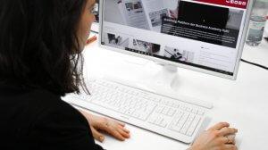 Eine Frau sitzt im Rahmen der Mitarbeiter Weiterbildung am PC und schaut sich das eLearning an