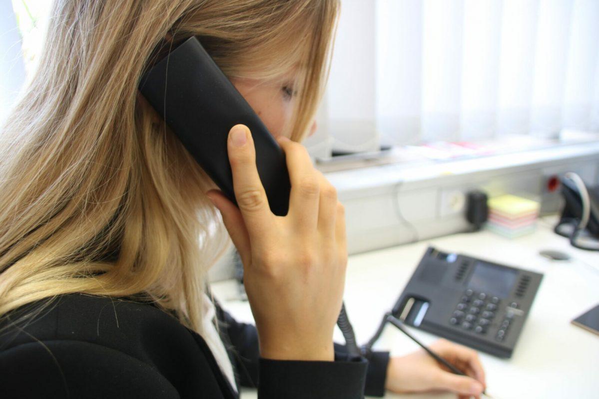 Junge Frau telefoniert an ihrem Arbeitsplatz
