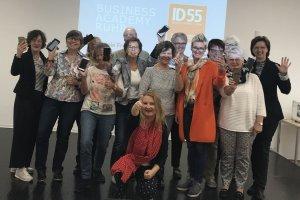 Man sieht die teilnehmenden Rentner der Kurse von ID55 in Herne, die mit der Gruppenleiterin in die Kamera lächeln. Sie nehmen an einer Reihe zum digitalen Lernen im Alter teil.