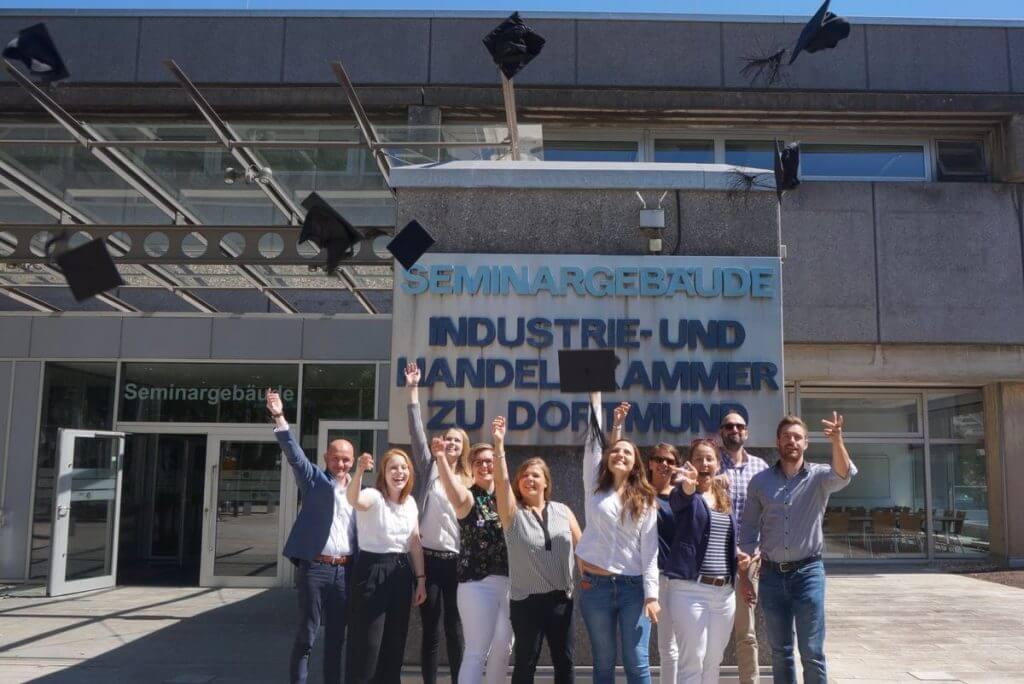 Sie werfen die Doktorhüte in die Luft: Die Teilnehmer im Online Marketing Manager Teilzeitkurs IHK Dortmund bei ihrem Abschluss