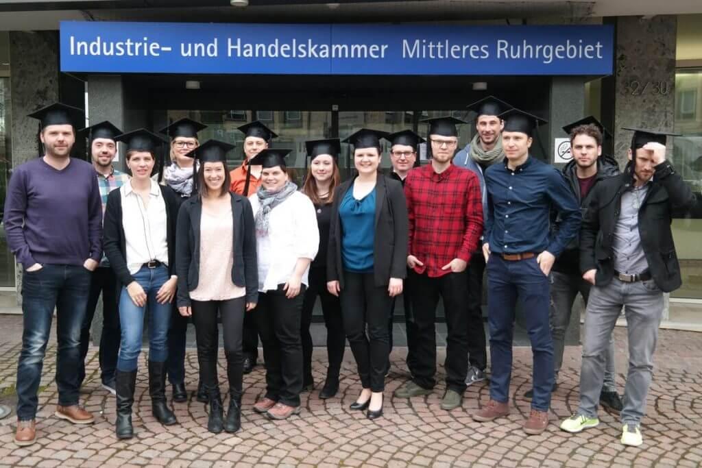 Das Bild zeigt die 15 Teilnehmer des Online Marketing Manager IHK Mittleres Ruhrgebiet Onlinekurs bei ihrem Abschluss vor dem Haupteingang der IHK