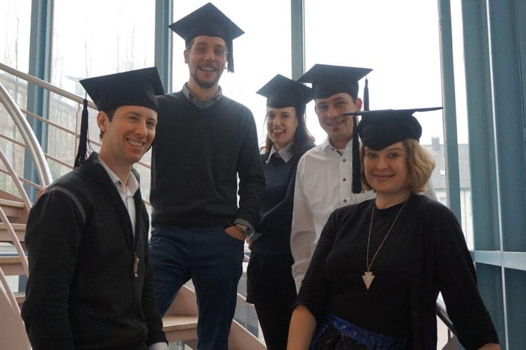 Das Foto zeigt die Absolventen des Online Marketing Manager IHK Mittleres Ruhrgebiet Onlinekurs mit ihren Doktorhüten auf der Treppe der IHK Bochum