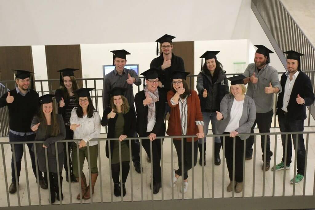 Das Bild zeigt die Teilnehmer des Online Marketing Manager IHK Nord Westfalen Teilzeitkurs mit ihren Doktorhüten