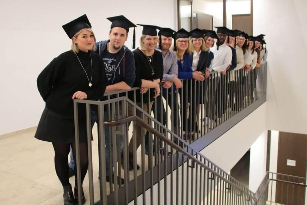 Das Foto zeigt die Teilnehmer Online Marketing Manager IHK Nord Westfalen Teilzeitkurs, die sich in einer Reihe am Treppengeländer aufgestellt haben