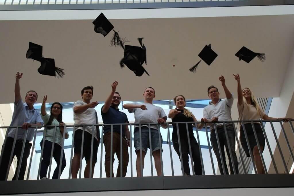 Sie werfen die Doktorhüte in die Luft: Die Teilnehmer im Online Marketing Manager IHK Nord Westfalen Teilzeitkurs bei ihrem Abschluss