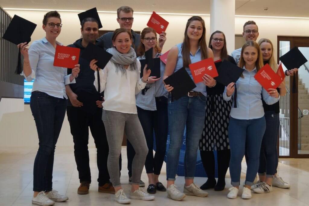 Das Bild zeigt die 10 Absolventen im Online Marketing Manager IHK Nord Westfalen Teilzeitkurs mit ihren Doktorhüten und Mousepads des Bildungsanbieters in den Händen.