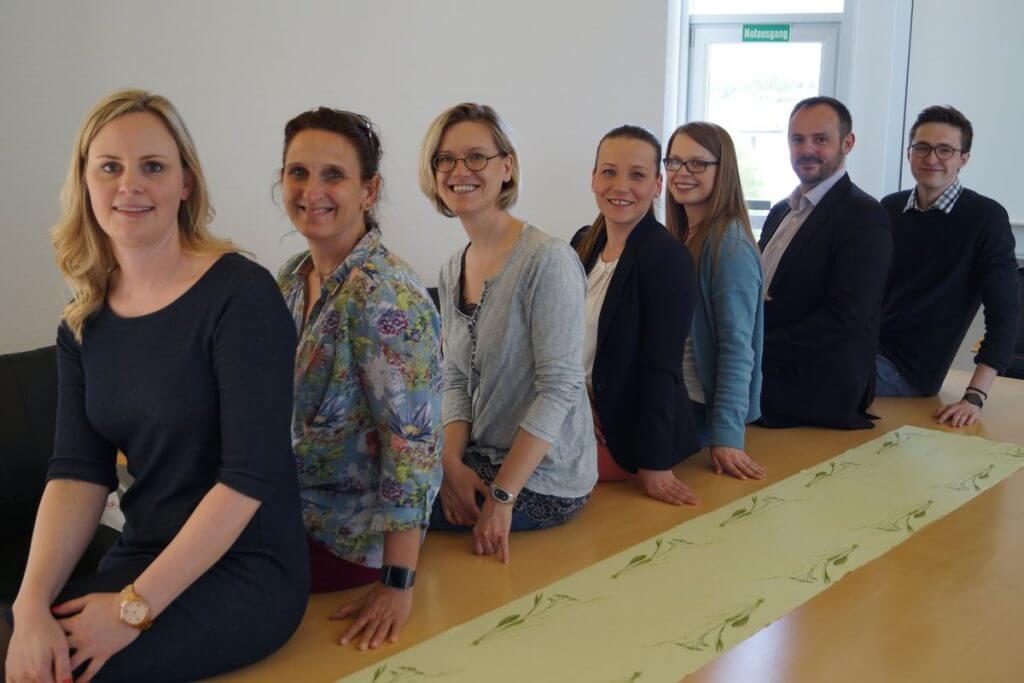 Das Bild zeigt die Absolventen im Online Marketing Manager IHK Siegen Onlinekurs wie sie auf einem Tische sitzen und in die Kamera lächeln.