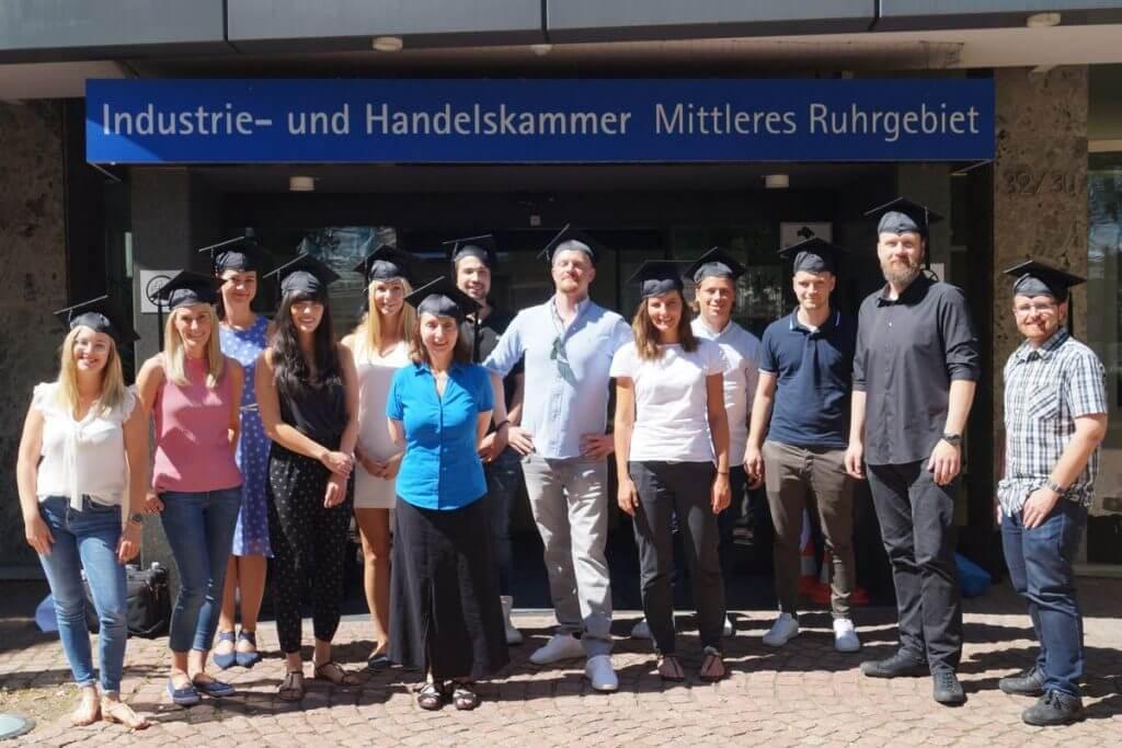 Das Foto zeigt die Absolventen im Online Marketing Manager IHK Mittleres Ruhrgebiet Onlinekurs vor der IHK Bochum. Sie tragen ihre Doktorhüte und lächeln in die Kamera.