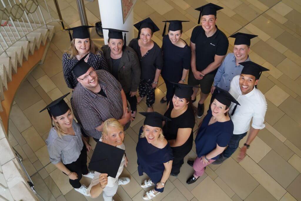 Das bild zeigt die Teilnehmer im Online Marketing Manager IHK Mittleres Ruhrgebiet Onlinekurs, wie sie im Kreis stehen und nach oben schauen. Das Bild wurde von einer Treppe aus aufgenommen.