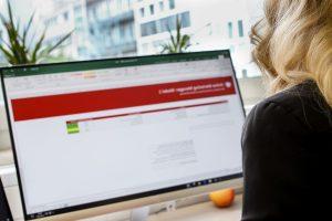 Eine Frau sitzt am PC und man schaut ihr über die Schulter auf den Monitor. Sie absolviert den Online Marketing Manager Onlinekurs in der Schweiz.