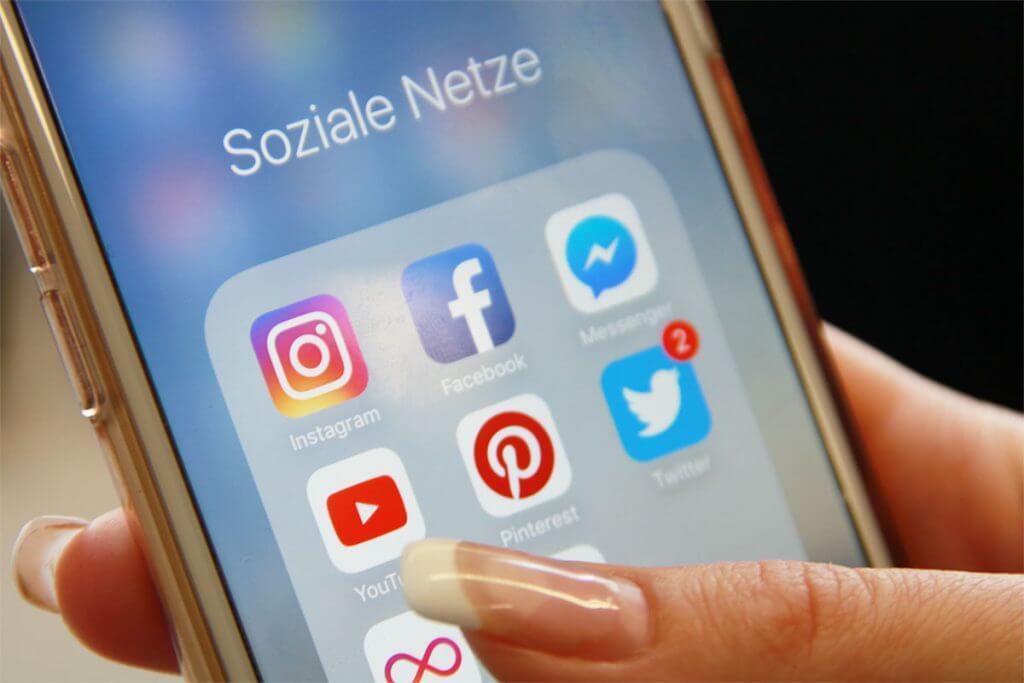 Das Bild zeigt ein Smartphone mit Icons zu verschiedenen sozialen Netwerken. Mittig befindet sich das Icon für Pinterest.