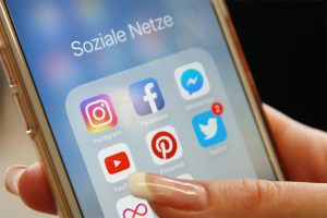 Das Bild zeigt ein Smartphone mit Icons zu verschiedenen sozialen Netwerken, darunter Instagram, Facebook, YouTube, Pinterest und Twitter.