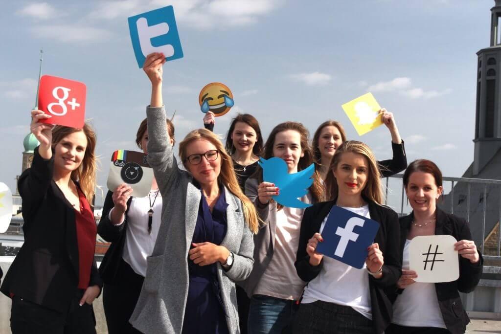 Auf dem Bild Social Media für KMU sind 8 Mitarbeiter zu sehen, die verschiedene Social Media Symbole in die Kamera halten