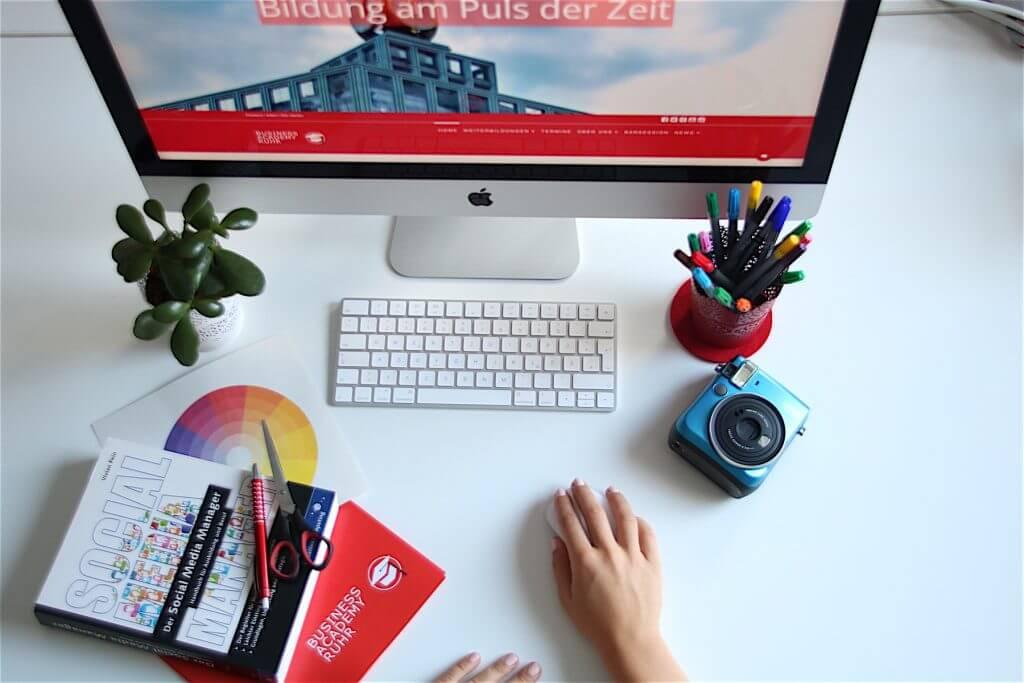 Das Bild Social Media für Kreative zeigt einen Schreibtisch mit Utensilien wie Kamera, Stifte, Computer, Zeichengeräte, Bücher