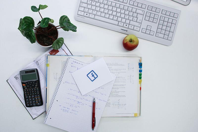 Gezeigt wird ein Bild zum Thema Social Media für Schulen. Auf einem Tisch liegen Schulunterlagen, ein Apfel, eine Tastatur und eine kleine Topfpflanze